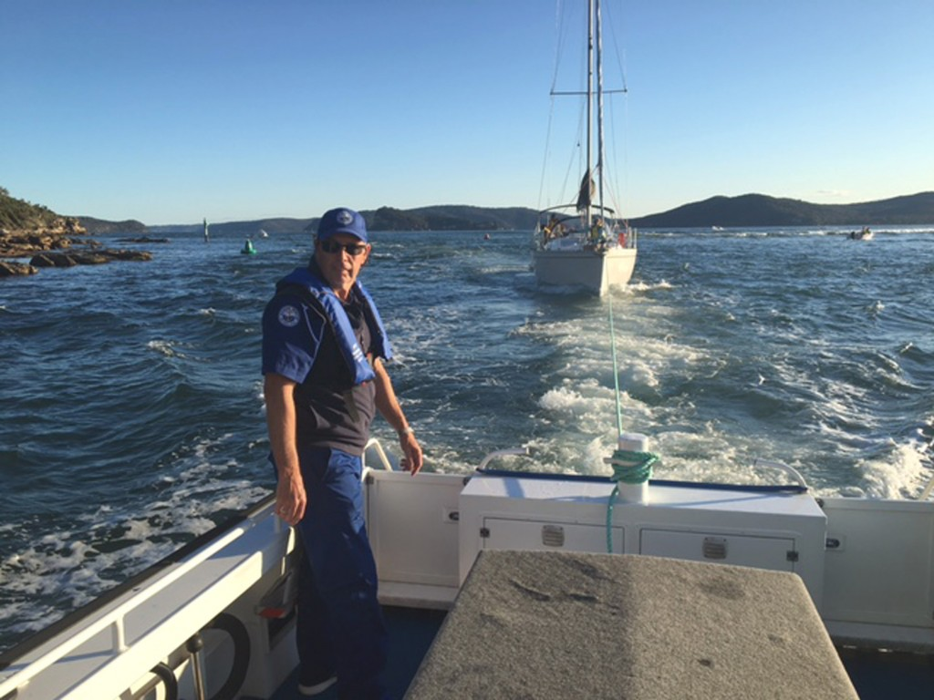 Crewman Bob Sullivan keeps check on yacht in tow at Box Head